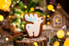 Holiday traditional food bakery. Gingerbread white christmas deer in cozy warm decoration with garland lights.  royalty free stock photo