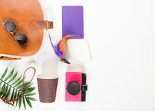 Holiday travel background. Brown cross bag, retro brown sunglasses, pink retro camera, lilac notebook, colorful headband, coffee c Royalty Free Stock Image