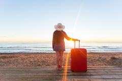 Holiday, travel and tourism concept - Beautiful woman with red suitcase over sandy beach background royalty free stock photography