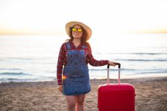 Holiday, travel and tourism concept - Beautiful woman with red suitcase over sandy beach background stock photo