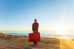 Holiday, travel and tourism concept - Handsome man with red suitcase over sandy beach background.  stock image