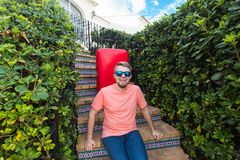Holiday, travel and tourism concept - Handsome man with red suitcase sitting on a stairs stock images