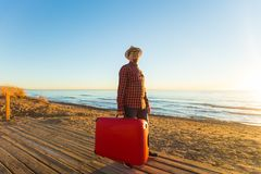Holiday, travel and tourism concept - Handsome man with suitcase over sandy beach background. Holiday, travel and tourism concept - Handsome man with suitcase stock image