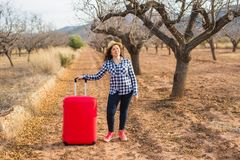 Holiday, travel and tourism concept - Young woman with red suitcase on summer nature stock image