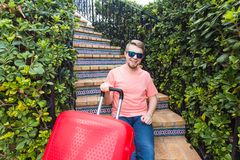 Holiday, travelling and baggage concept - young man with suitcase sitting on stairs royalty free stock photos