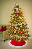 Holiday tree decorated with ornaments. Festive Christmas tree with tinsel, baubles, and ornaments standing beside a sofa in a living room Stock Photography