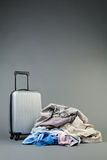 Holiday or Trip Luggage. A compact suitcase next to a pile of casual clothes Stock Image