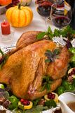 Holiday turkey. Garnished roasted turkey on holiday decorated table with pumpkins and glasses of red wine Stock Photo