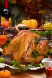 Holiday turkey. Garnished roasted turkey on holiday decorated table with pumpkins and glasses of red wine Royalty Free Stock Image