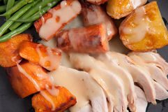 Holiday turkey dinner. Traditional turkey dinner with crispy skin, turkey slices and fresh roasted vegetables smothered in gravy perfect for Christmas dinner and Royalty Free Stock Image