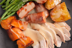 Holiday turkey dinner. Traditional turkey dinner with crispy skin, turkey slices and fresh roasted vegetables smothered in gravy perfect for Christmas dinner and Royalty Free Stock Photo