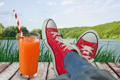 Holiday with views of the water and the woods with a glass of ju Royalty Free Stock Images