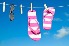 Holiday Washing Line. Against blue sky with flip flops and sunshades - reflection of beach in sunglasses Royalty Free Stock Photography
