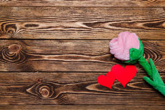 Holiday/wedding/valentine Day background. Holiday/romantic/wedding/valentine Day background with plush rose and two paper red hearts on wooden table Stock Images