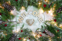 Holiday welcome sign. With rope heart and green Christmas tree garland border, snow and lights on antique rustic wooden background Stock Image