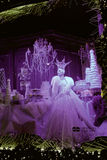Holiday windows on Fifth Avenue. Lavender colorglass case sets a festive table, crystal chandeliers, and a lady's figure in a beautiful dress. Christmas time in stock photo