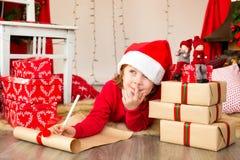 Holiday wish list. Girl writing a christmas wish list Stock Photo