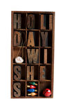 Holiday wishes in letterpress type in an old wood. The phrase 'holiday wishes' in a type case with vintage Christmas light bulbs, a red jingle bell and a baby stock photography