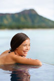Holiday woman swimming at beach on Hawaii travel. Asian chinese young lady relaxing in infinity pool in luxury hotel resort on Waikiki beach in Honolulu, Oahu Royalty Free Stock Photo