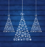 Holiday wooden background with Christmas pines made of snowflake Royalty Free Stock Photo