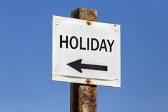 Holiday word and arrow signpost. On clear sky background. Motivational sign Royalty Free Stock Images