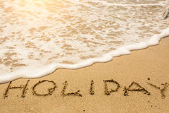 Holiday - word drawn on the sand beach Royalty Free Stock Photography