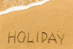 Holiday - word drawn on the sand beach Royalty Free Stock Images
