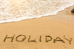 Holiday - word drawn on the sand beach Royalty Free Stock Image