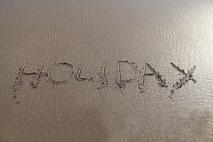 Holiday word written in sand. HOLIDAY word written in the sand of the beach. Ideal for beach holiday promotions Royalty Free Stock Photo