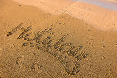 Holiday word written in sand. Summer beach concept Stock Photography