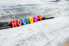HOLIDAY words on wood background. HOLIDAY words on wooden background Royalty Free Stock Photo