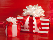 Holiday Wrapped Presents. Two holiday gifts wrapped in red and white stripes with red and white bows against a red background Stock Photo