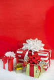 Holiday Wrapped Presents. Four brightly wrapped holiday gifts: red and white stripes with red and white bows and gold with red ribbons against a red and white Royalty Free Stock Image