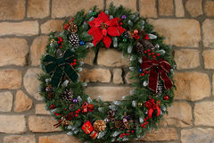 Holiday Wreath. Home made holiday wreath hanging on stone wall Stock Photography