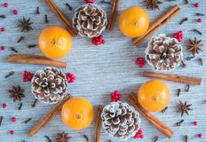 Holiday wreath arrangement of oranges, pine cones, spices, and red berries stock photos