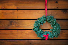 Holiday wreath hanging against wood planks Royalty Free Stock Image