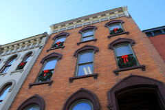 Holiday wreaths decorating windows of old buildings Royalty Free Stock Images