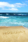 Holiday written in beach sand Royalty Free Stock Photo