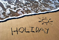 Holiday written in sand. The word holiday written in sand with a wave washing in Stock Photo