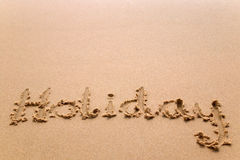 Holiday written in sand. The word 'Holiday' written in sand at the beach Stock Image