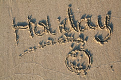 Holiday written in sand. Word holiday written in sand with smiley face Royalty Free Stock Photos