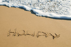 Holiday written on sand. The word 'holiday' written onto sand surface about to be washed away Stock Photography