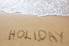 Holiday written in sand. On the beach Royalty Free Stock Photos