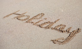 Holiday written on the sand. Written on the sand of the beach: Holiday Royalty Free Stock Image