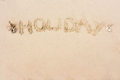 HOLIDAY written in the sand on the beach with copy space for t Stock Image