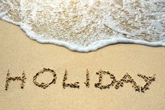 Holiday written on sand beach near sea. Holiday written on the sand beach near sea Stock Photo