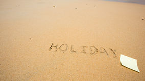 Holiday written in the sand at the beach with post it Royalty Free Stock Images