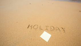 Holiday written in the sand at the beach with post it Stock Images