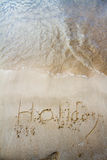 Holiday written in the sand on the beach. Waves in the background Royalty Free Stock Photography