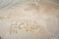 Holiday written in the sand. On the beach waves in the background Royalty Free Stock Images